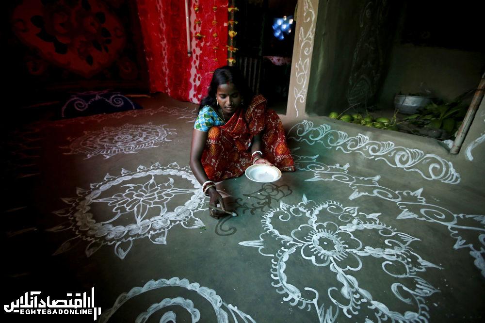پوتیمای ۲۷ ساله مشغول طراحی با رنگ برنجی برای جشن در جزیره هندی گورامارا
