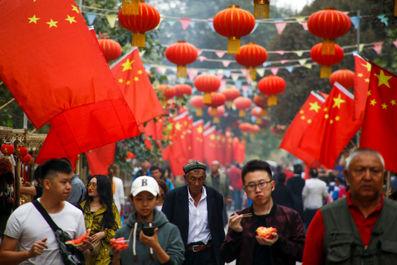 مردم در حال عبور از کنار پرچم چین در کاشگار ، منطقه خودمختار اویگور چین