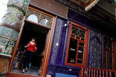 خدمتکار در حال سرو نوشیدنی در کاشگار منطقه خودمختار اویگور چین
